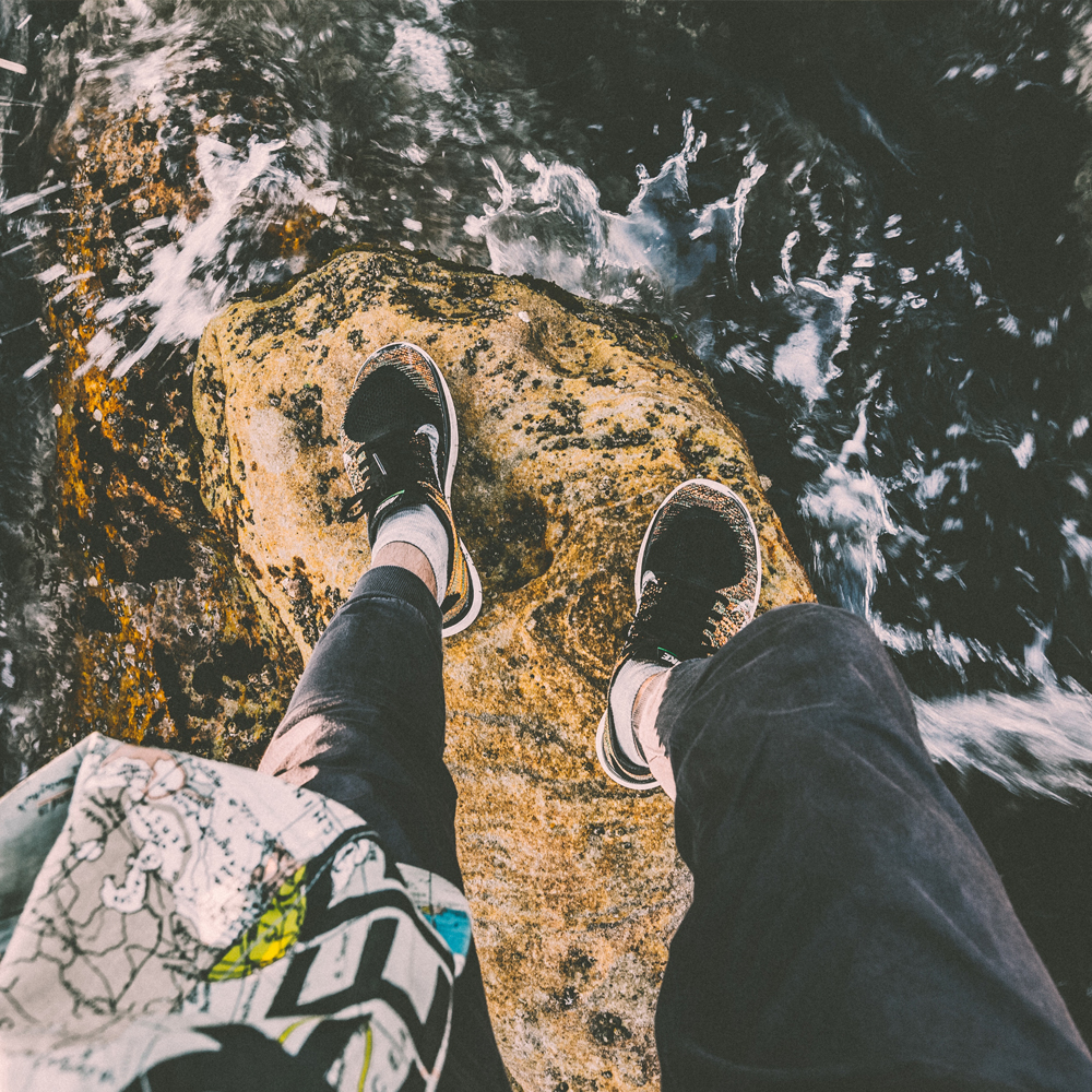 shot of legs on a rock above the waterfall